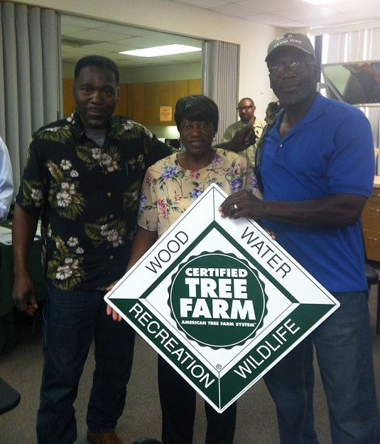 Mrs. Campbell and her family holding a Tree Farm sign.