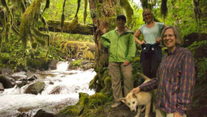 Three women and a dog hiking along a forested stream.