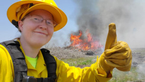 County Forester Regine Skelton giving a thumbs-up in front of a prescribed fire.
