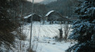 Snowy barns in forest and valley