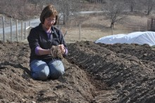 Woman smiling down whilst holding dirt